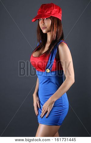 Sexy girl wearing a plumber costume for cosplayer over a gray background poster