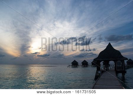 Beautiful sunset on the Thulhagiri Island (Maldives) with silhouettes of overwater bungalows