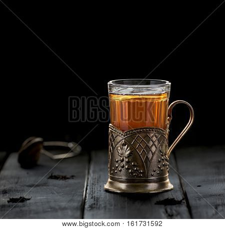 Traditional Russian tea served in glass with vintage brass glass holder. Podstakannik. Concept of tradition. Concept of tea time. Selective focus. Negative space. Copy space.