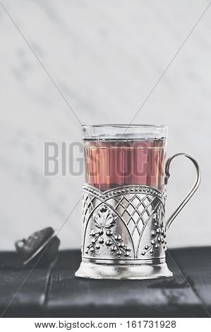 Traditional Russian tea served in glass with vintage brass glass holder. Podstakannik. Concept of tradition. Concept of tea time. Retro vintage edit. Selective focus. Negative space. Copy space.
