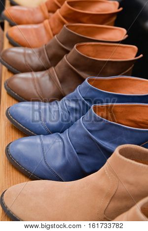 Row of women's leather boots on wooden table Shoe shop