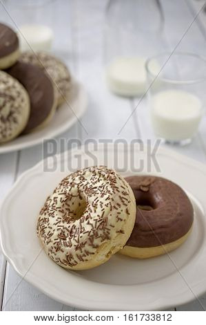 Sweet homemade dessert doughnuts with white and milk chocolate in rustic setting on white wood boards and glasses of milk and milk bottle. Selective focus on front doughnut. Concept of comfort food. Concept of home baking. Concept of dessert.