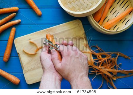 Male hands peeling an orange carrot on blue background. Concept of healthy food preparation. Peeled carrots in steamer. Hands in frame. Top down view. Flat lay.