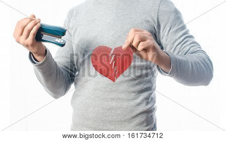 Heart and a stapler in the hands of bonded heart, red whole