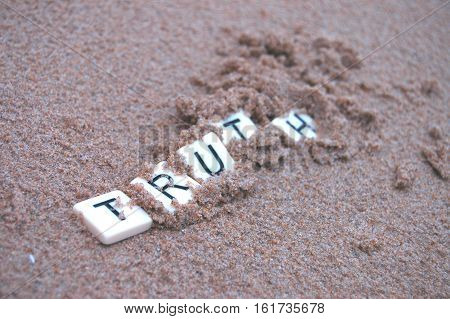 Post Truth: Letters spelling 'truth' becoming buried in sand