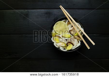 Japanese soup with udon noodles mushrooms leeks and lime. Concept of eating. Concept of asian food. Concept of japanese food. Top down. Flat lay. Selective focus.