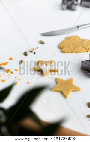 Vertical Baking Scene of Orange and Cardamom Festive Star Biscuits on White Table