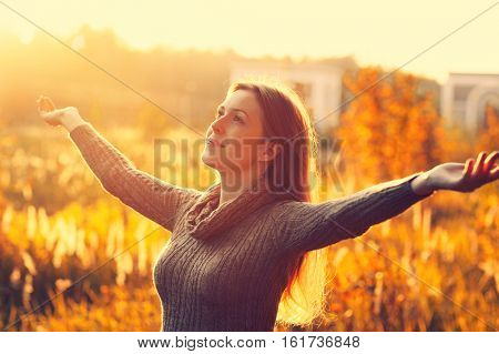 Young romantic woman enjoying good warm autumn weather and feeling free and positive. Vibrant sunset colors.