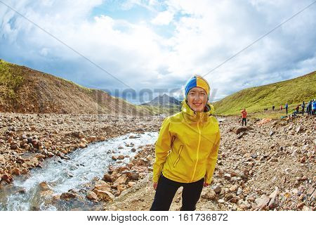 Vacation in iceland. happy woman hiker in the Islandic mountains. Trek in National Park Landmannalaugar, Iceland. woman smiling and posing near the creek against a cloudy sky
