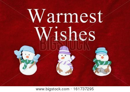 Warmest Wishes greeting Red plush fabric with three snowmen background with text Warmest Wishes