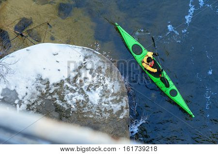 man paddles a green kayak on the river near the shore, kayaking