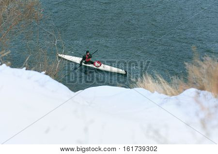 man paddles a white kayak on the river near the shore, kayaking