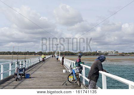 HARVEY BAY, AUSTRALIA - December 6, 2016: People enjoying recreational fishing from the pier in Harvey Bay Australia