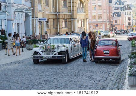 Kiev Ukraine - September 20 2015: Luxury wedding car and pedestrians in the historic part of Kiev