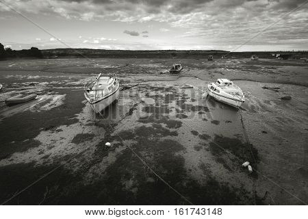 Dramatic evening in Cockwood. The harbor at low tide. Black and white photo. Devon. England