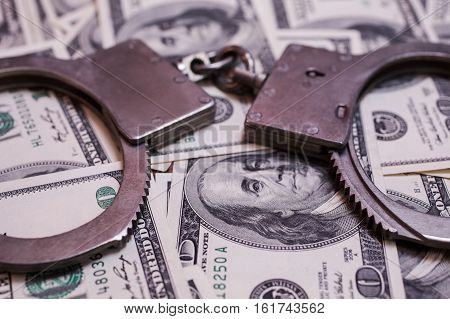money and the law handcuffs on money hundred dollar bills front face side and handcuffs. background of dollars savings taxes and law