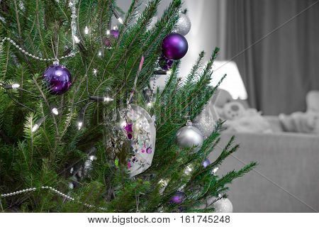 Christmas tree with silver and purple baubles against a desaturated living room background and vibrant sharp green needles