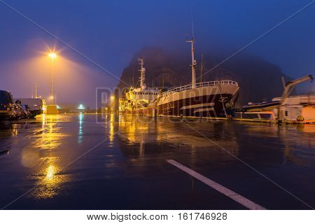 Ship docked in the harbor of Heimaey in the Westman Islands (Vestmannar) south from Iceland. In the background volcanic rock formations that shield the harbor from rough seas disappear in the fog.