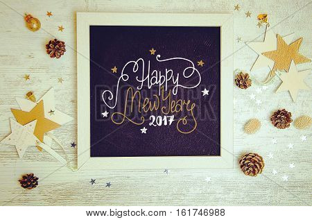 New Year decorations and objects flat lay photo with black chalkboard frame and hand drawn inscription. Happy New Year 2017 gift lettering on black board.