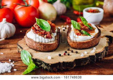 Bruschettas with Dried Tomatoes and Spicy Sauce on Cutting Board