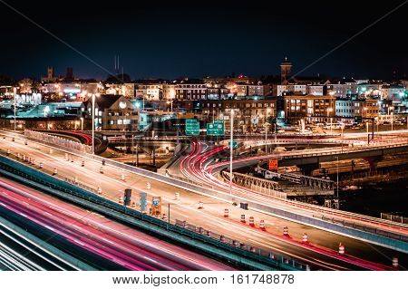 Night time cityscape long exposure featuring highway and buildings