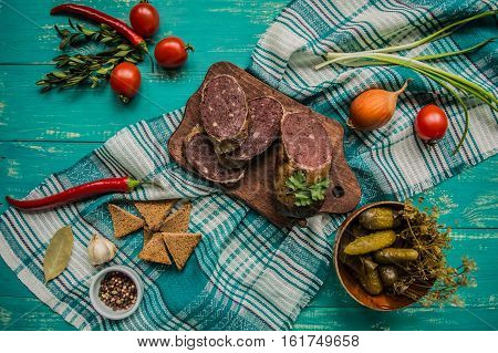 Homemade blood sausage with offal on a turquoise wooden background. top view