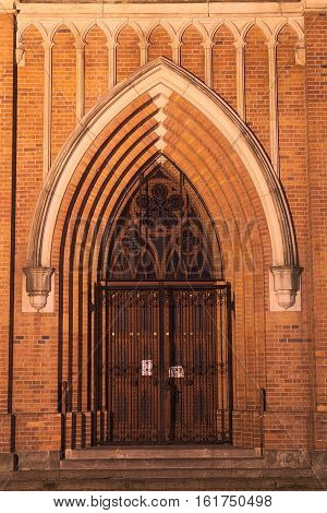 The photo shows the gates leading to the neo-Gothic church tower located in the town of Zagan in western Poland. It is night, the church is illuminated by electric lamps.