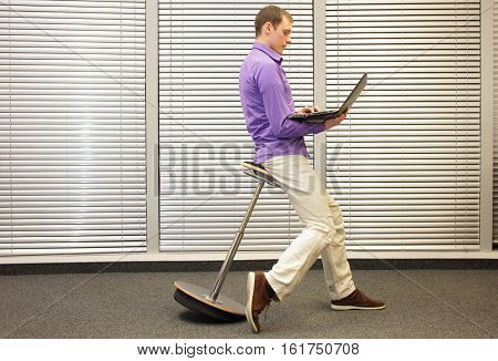 correct position during office work - man sitting on pneumatic stool, working with laptop in his office