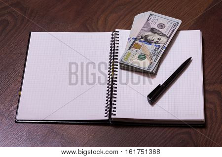 black pen note book page and money a place for records business plan money background hundred dollar bills front side. background of dollars new hundred-dollar bil face the evolution of the bill in one hundred dollars copyspace