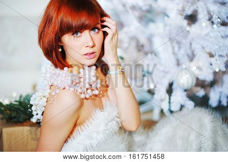 Bright Pretty Model In A White Fur Cape Around The Christmas Artificial Christmas Trees With Decorat