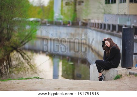 Young Sad Girl Sitting On A Concrete Slab Near The Canal, Head Down.