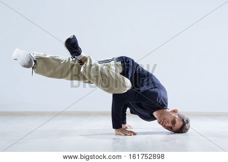 Hip hop dancer performing isolated over white background. Hip hop performer is standing on the hand.