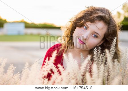 Portrait of young woman with dry wheat grain grass illuminated in sunlight