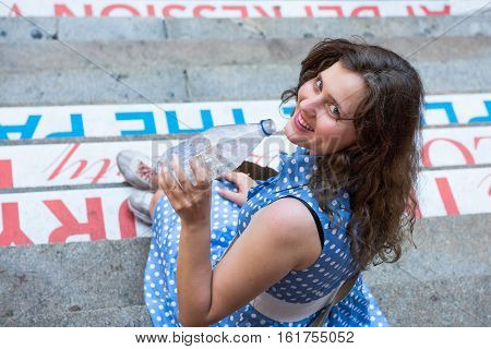 Young woman with blue polka dot dress sitting on steps drinking carbonated water in a clear bottle and laughing