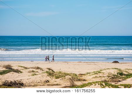 Pismo Beach USA - February 14 2016: Dunes in California beach with people walking