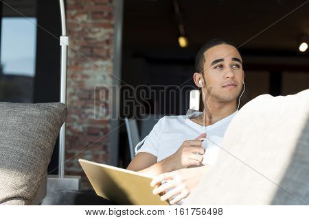 Handsome Guy Using A Tablet And Listening Music