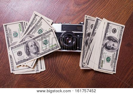 camera and money. background of dollars new hundred-dollar bil face copyspace the work of the photographer the photographer earnings in photos