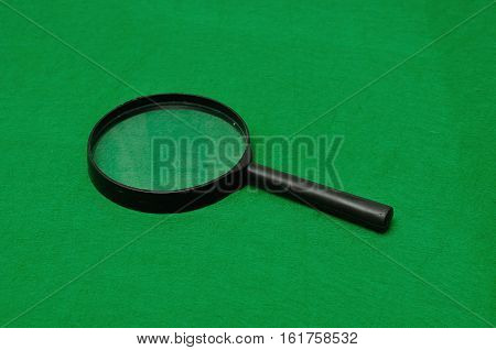 Magnifying glass isolated on a green background