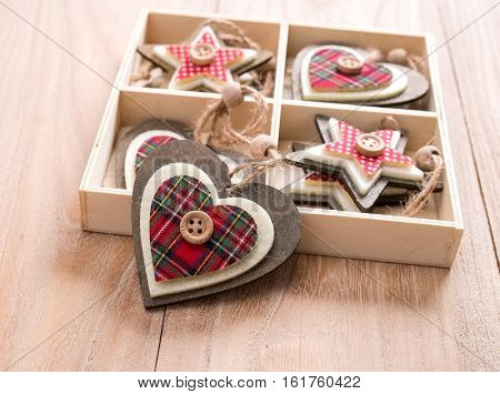 Christmas decoration red, white, gingham, stripes fabric stars and heart shape with buttons on rustic Elm wood background