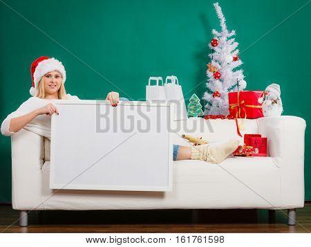 Woman In Santa Hat Holding White Blank Board