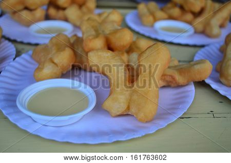 Close up deep-fried dough stick (well known as patongkoh) with sweetened condensed milk dip