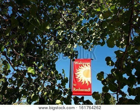 A red and yellow banner framed by tree branches welcoming people to Redmond in Central Oregon on a fall day.