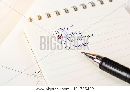 Choosing the right date on diary with calendar page with pen. Time management concept.