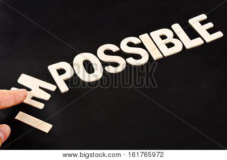 man hand spelling the word impossible from wooden letters taking out the letter I M so it written possible. success and challenge concept.