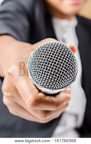 Hand holding a microphone conducting a business interview.