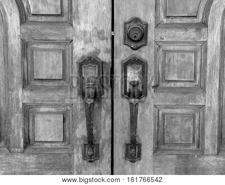 Old teak wooden door with rusty latch black and white