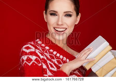 christmas, x-mas, winter, happiness concept - smiling woman in sweater with gift boxes