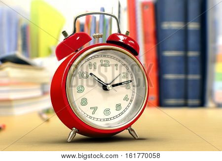 Red alarm clock on study desk with blurry background