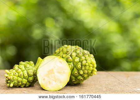 Noni fruit and noni slice on wooden table and green background.Fruit for health and herb for health.