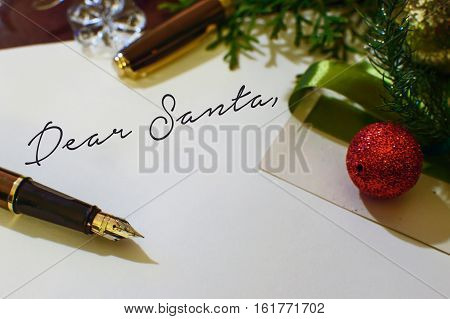 Dear Santa writing letter to Santa adult Christmas writer theme card with room for copy paper and fountain pen and ribbon on desk with Christmas ornaments under Christmas tree with evergreen branches